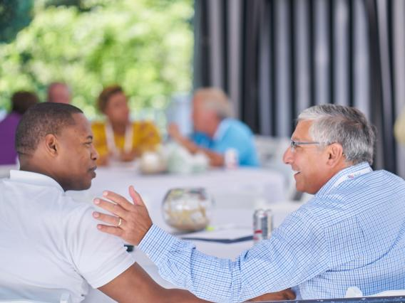 two business men talking at an outdoor group table